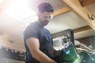 Steel worker using sander in workshop - CAIF11230