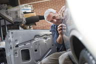 Focused auto body worker examining panel on car - CAIF11233