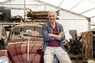 Portrait confident mechanic leaning on classic car in auto repair shop - CAIF11248