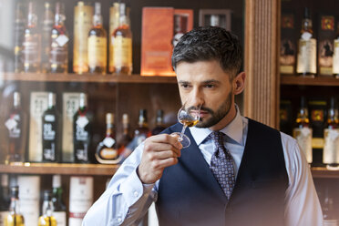 Well-dressed man whiskey tasting - CAIF11278