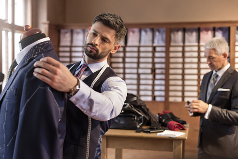 Tailor adjusting suit on dressmakers model in menswear shop - CAIF11287
