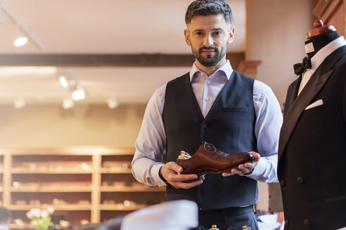 Portrait confident businessman holding dress shoe in menswear shop - CAIF11290