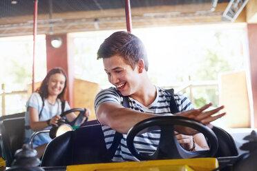 Smiling young man riding bumper cars at amusement park - CAIF11323