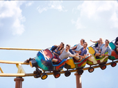 Friends cheering and riding roller coaster at amusement park - CAIF11326