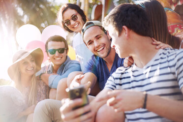 Smiling friends texting with cell phone at amusement park - CAIF11329