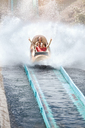 Enthusiastic friends cheering and riding water log amusement park ride - CAIF11335