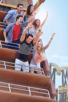 Enthusiastic friends cheering on amusement park ride - CAIF11338