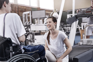 Smiling physical therapist talking to man in wheelchair - CAIF11341