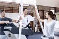 Smiling man high fiving physical therapist - CAIF11344