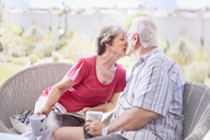 Senior couple kissing and drinking coffee on patio - CAIF11371