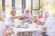 Senior adults toasting wine glasses at patio lunch - CAIF11377