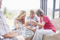 Senior women using cell phone on patio - CAIF11389