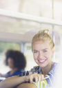 Portrait smiling blonde woman holding cell phone on bus - CAIF11431