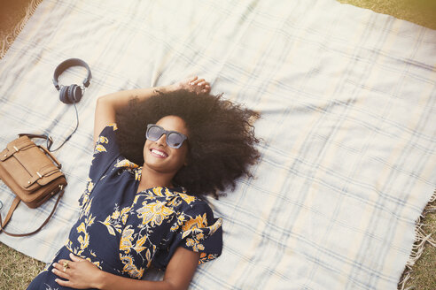 Overhead view smiling woman with afro laying on blanket outdoors - CAIF11437
