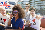 Portrait enthusiastic friends with British flag riding double-decker bus - CAIF11443
