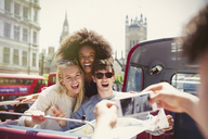 Enthusiastic friends being photographed on double-decker bus - CAIF11452