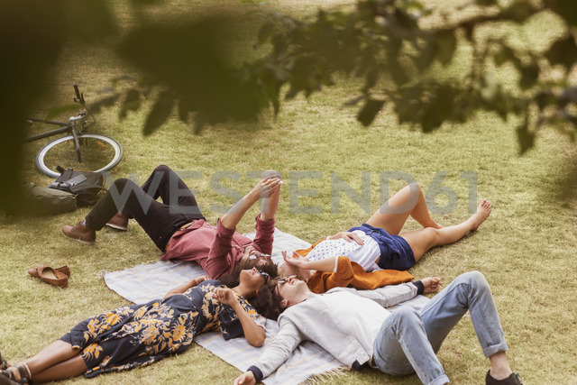 Friends taking selfie laying in circle on blanket in park - CAIF11458