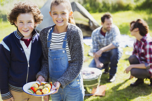 Portrait smiling brother and sister with vegetable skewers at campsite - CAIF11488