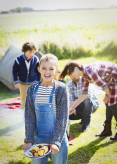Portrait smiling girl with vegetable skewers at sunny campsite - CAIF11494