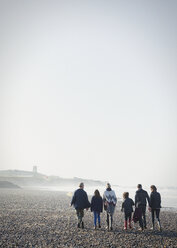 Multi-generation family walking on sunny beach in a row - CAIF11497