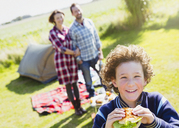 Portrait smiling boy eating hamburger with parents at sunny campsite - CAIF11503
