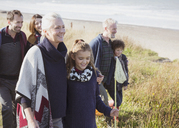 Smiling multi-generation family walking in beach grass - CAIF11506