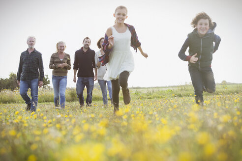 Energetic brother and sister running in meadow with family in background - CAIF11512