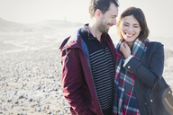 Smiling brunette couple standing on sunny rocky beach - CAIF11518