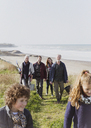 Multi-generation family walking on sunny grass beach path - CAIF11521