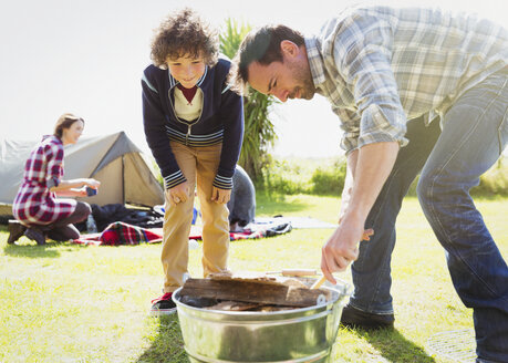 Father and son building campfire - CAIF11524