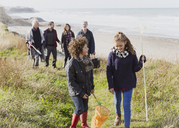 Multi-generation family with nets walking on sunny grass beach path - CAIF11530