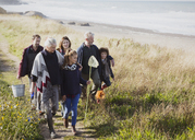 Multi-generation family walking with nets and bucket on sunny grass beach path - CAIF11533