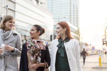 Businesswomen walking with coffee in city - CAIF11554