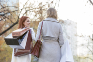 Women carrying shopping bags in city park - CAIF11560