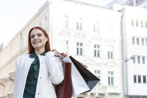 Smiling woman carrying shopping bags in city - CAIF11563