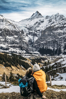 Couple looking at snowy mountain view, Grindelwald, Switzerland - CAIF11578