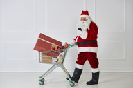 Santa Claus carrying Christmas presents in a shopping cart while looking at cell phone - ABIF00108