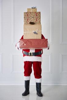 Santa Claus holding stack of Christmas presents - ABIF00111
