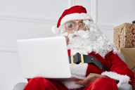 Santa claus using laptop with magnifier - ABIF00120