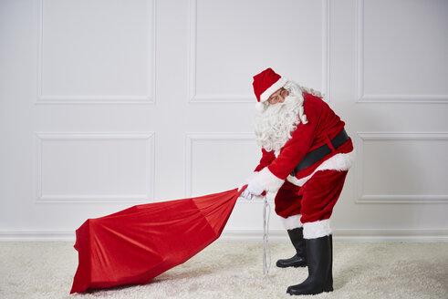 Santa claus pulling heavy sack - ABIF00123