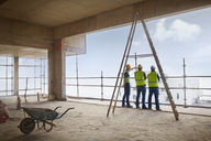 Construction workers at highrise construction site - CAIF11592