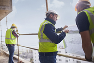 Construction worker and engineer reviewing blueprints at highrise construction site - CAIF11595