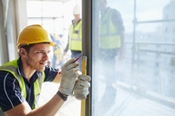 Construction worker measuring window at construction site - CAIF11598