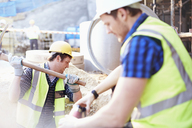 Construction workers digging at construction site - CAIF11601