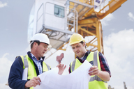 Construction worker and engineer reviewing blueprints below crane at construction site - CAIF11604