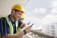 Construction worker texting at highrise construction site - CAIF11613