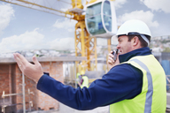 Construction worker with walkie-talkie at construction site - CAIF11616