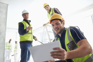 Construction workers with digital tablet at construction site - CAIF11619