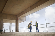 Construction workers handshaking at highrise construction site - CAIF11622