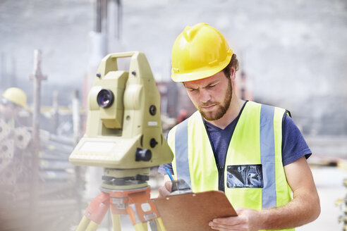 Engineer with clipboard behind theodolite at construction site - CAIF11631
